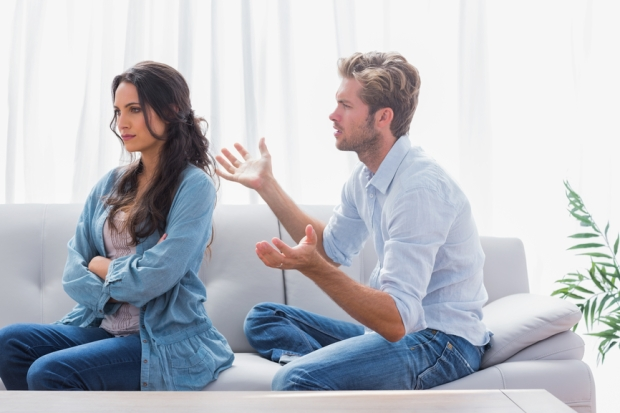 Woman with arms crossed is sulking while her partner is talking to her